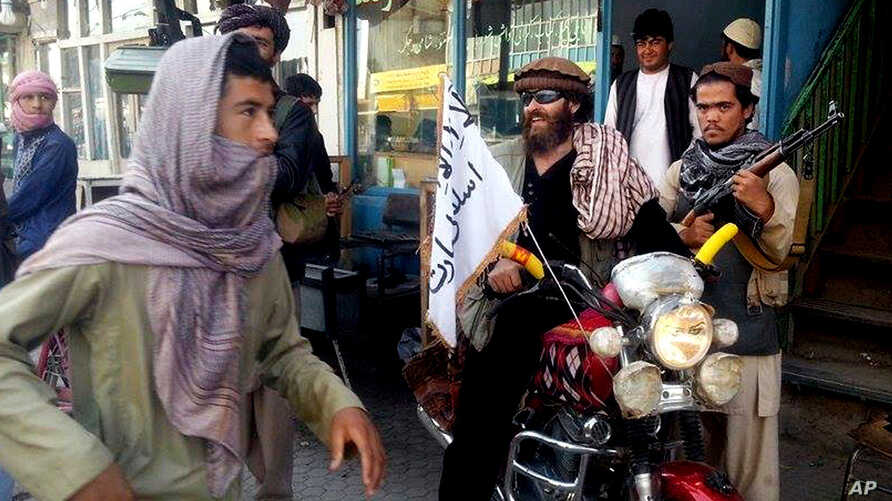 FILE - a Taliban fighter sits on his motorcycle adorned with a Taliban flag on a street in Kunduz, Afghanistan.