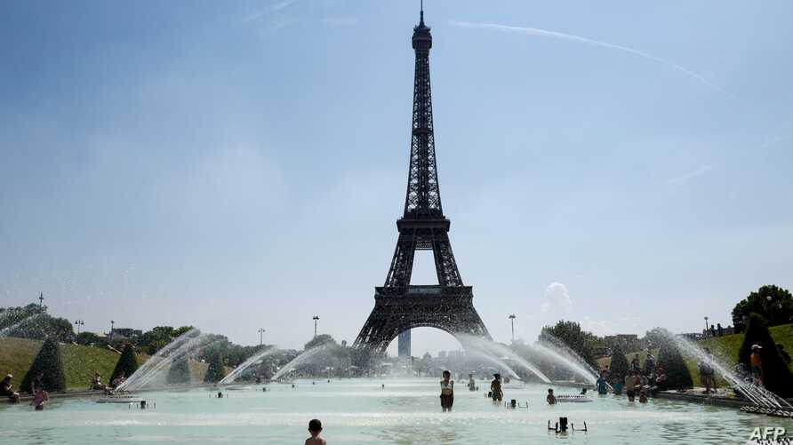People cool themselves at the Trocadero Fountain in front of The Eiffel Tower in Paris on July 27, 2018, as a heatwave continues across northern Europe.