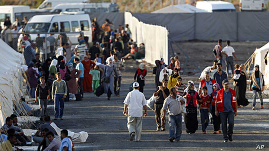 Newly arrived Syrian refugees walk to their tents in the Turkish border town of Reyhanli in Hatay province June 23, 2011, as others who are already placed rest in front of their tents.