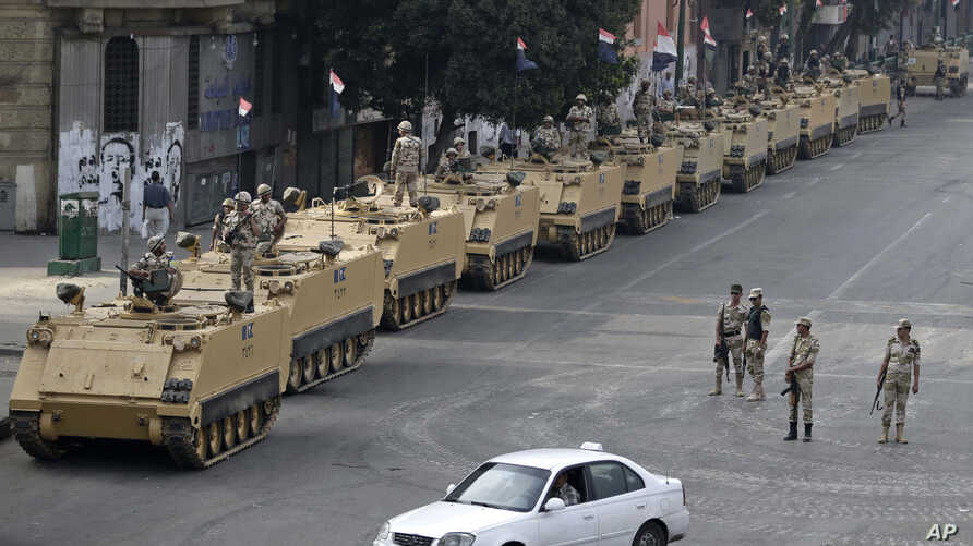 FILE - Egyptian army soldiers take their positions on top and next to their armored vehicles to guard an entrance of Tahrir Square, in Cairo. Obama administration is poised to slash hundreds of millions of dollars in military and economic assistance