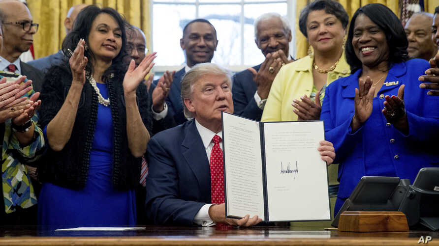 President Donald Trump holds up the Historically Black Colleges and Universities HBCU Executive Order after signing it, Feb. 28, 2017, in the Oval Office in the White House in Washington.
