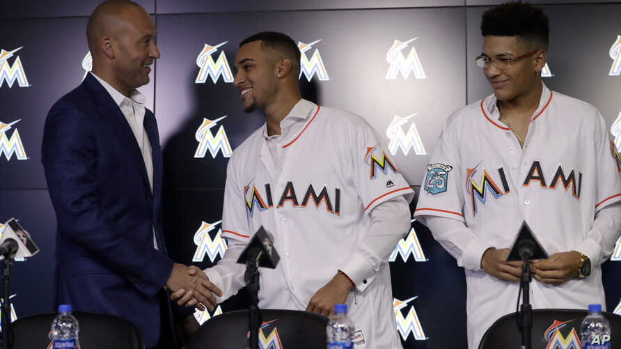 Miami Marlins CEO Derek Jeter, left, shakes hands with Victor Victor Mesa, center, as his brother Victor Mesa Jr., looks on during a news conference, Oct. 22, 2018, in Miami. The outfielders from Cuba were signed to minor league contracts with the Ma