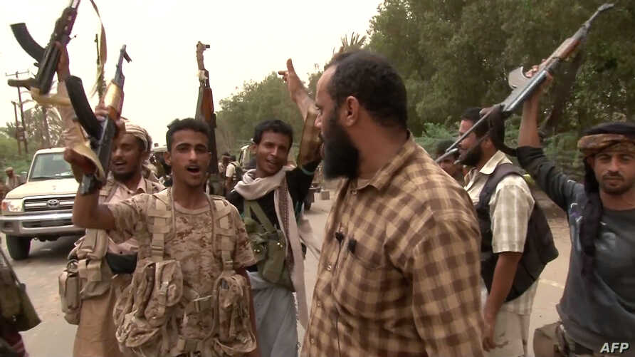 This image grab taken from a AFPTV video shows Yemeni pro-government forces gathering at the south of Hodeida airport, in Yemen's Hodeida province, June 15, 2018.