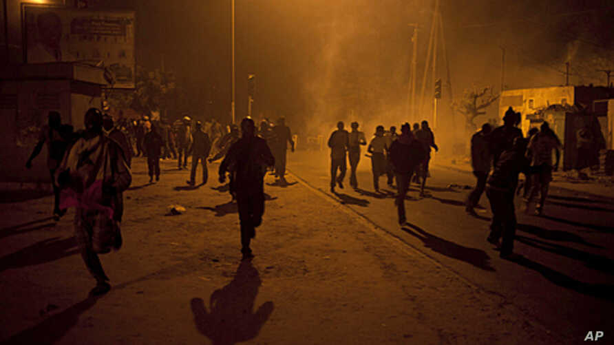 Anti-government protesters run from tear gas in Dakar on January 27, 2012.