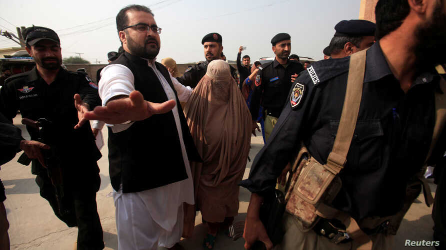 Policemen escort Sharbat Gula (in burqa), the green-eyed Afghan woman who became a symbol of her country's wars 30 years ago when her photo as a girl appeared on the cover of National Geographic magazine, as she arrives at a court in Peshawar, Pakist