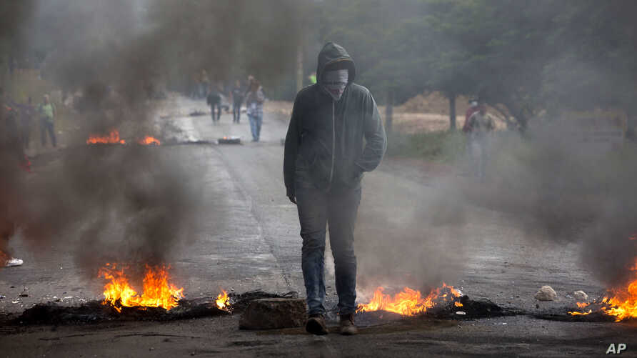 An anti-government protester stands at a burning barricade erected by protesters to block the road to Valle de los Angeles, on the outskirts of Tegucigalpa, Honduras, Dec. 7, 2017.