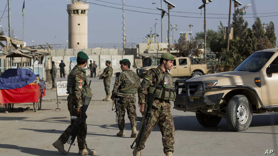 Afghanistan's National Army soldiers guard, blocking the main road to the Bagram Airfield's main gate in Bagram, north of Kabul, Afghanistan, Saturday, Nov. 12, 2016.