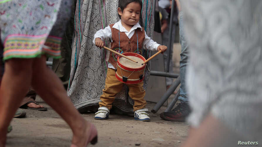 A child member of Cantagallo, an Indigenous Shipibo-Konibo community, plays the drums during a visit of Peru's President Pedro Pablo Kuczynski, in Lima, Peru Dec. 16, 2016.