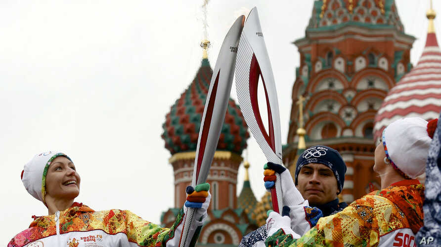 Russian Olympic gold medalists, synchronized swimmer Anastasya Davydova (L) and former artistic gymnast Svetlana Khorkina (R),  join their torches during a relay of the Olympic flame in Moscow, Oct. 7, 2013.