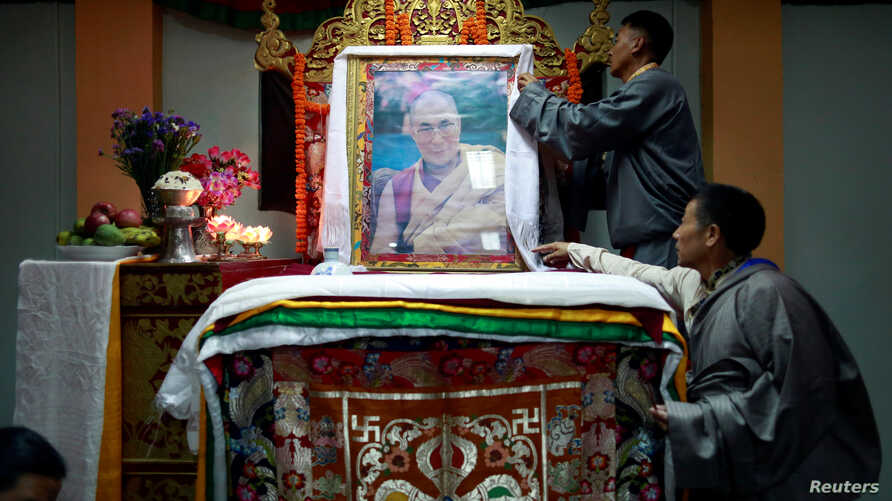 Tibetans arrange a portrait of the Dalai Lama during a function organized to mark his 82nd birthday in Lalitpur, Nepal, July 6, 2017.