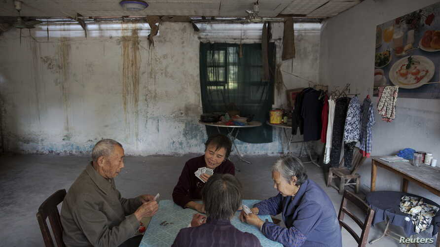 Patients and their relatives play cards in a dilapidated service building at Yangjia Hospital in Wuyi County, Zhejiang Province, China, Oct. 19, 2015.