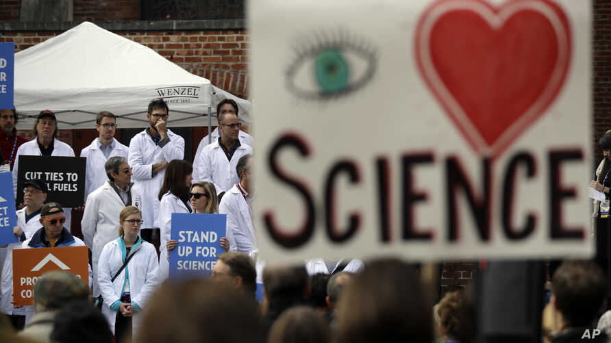 FILE - People hold signs as they listen to a group of scientists speak during a rally in conjunction with the American Geophysical Union's fall meeting, Dec. 13, 2016, in San Francisco. The rally was to call attention to what scientist believe is unw