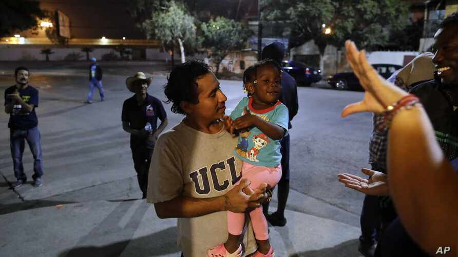 Guatemalan Elvin Vazquez (center) holds a Haitian girl immigrating with her family at a migrant shelter in Tijuana, Mexico, Nov. 14, 2016. Thousands of Haitians have arrived at the U.S. border with Mexico in recent months, many after traveling 7,000