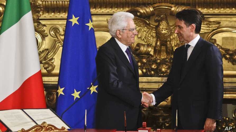 Italian President Sergio Mattarella (L) shakes hands with Premier Giuseppe Conte during the swearing-in ceremony for Italy's new government at Rome's Quirinale Presidential Palace, June 1, 2018.
