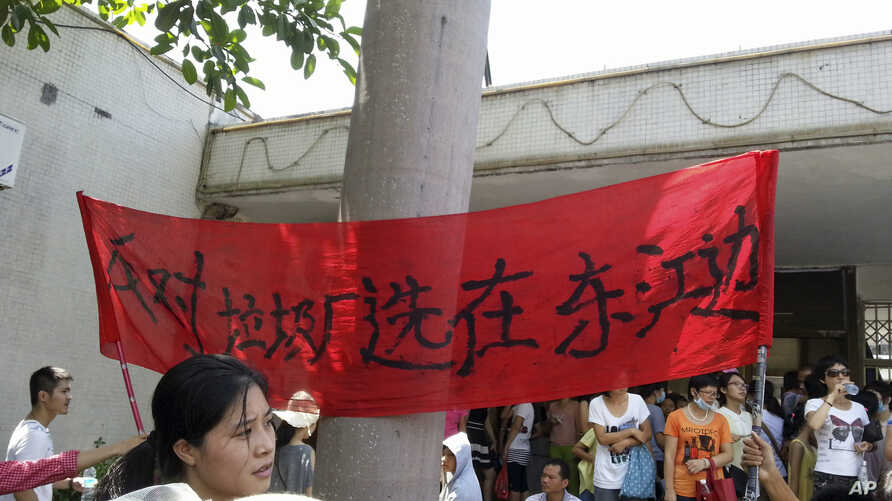 """Protesters hold up a banner which reads """"Against garbage incinerator along east river"""" in Boluo county in south China's Guangdong province, Sept. 14, 2014."""