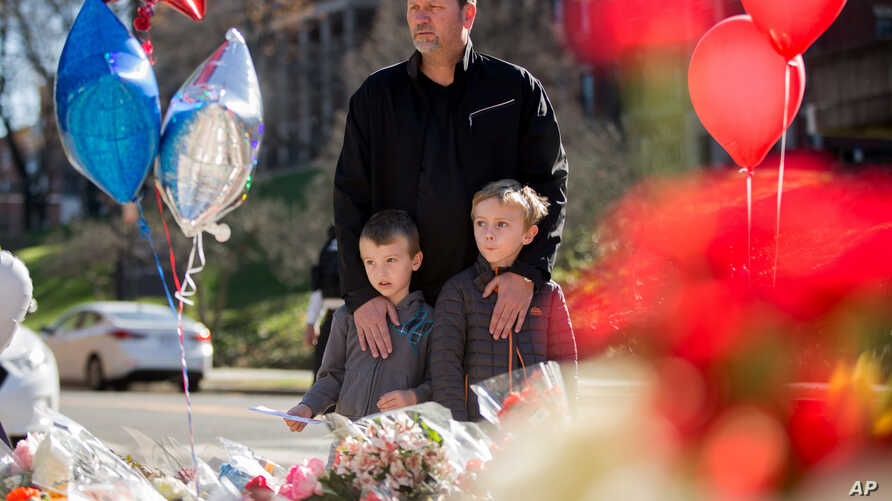 A man and his two sons are seen at a memorial outside the gates of the French Embassy in Washington, Nov. 15, 2015.