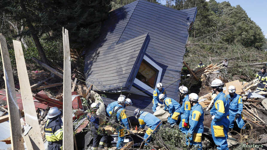 Rescue workers search for survivors from a house damaged by a landslide caused by an earthquake in Atsuma town, Hokkaido, Japan, Sept. 6, 2018.