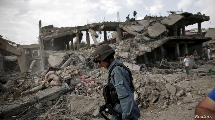 FILE - An Afghan policeman walks at the site a truck bomb blast in Kabul, Aug. 7, 2015. A U.S. Green Beret admitted killing a man in Afghanistan he suspected was a bombmaker. There is enough evidence to charge him with murder.