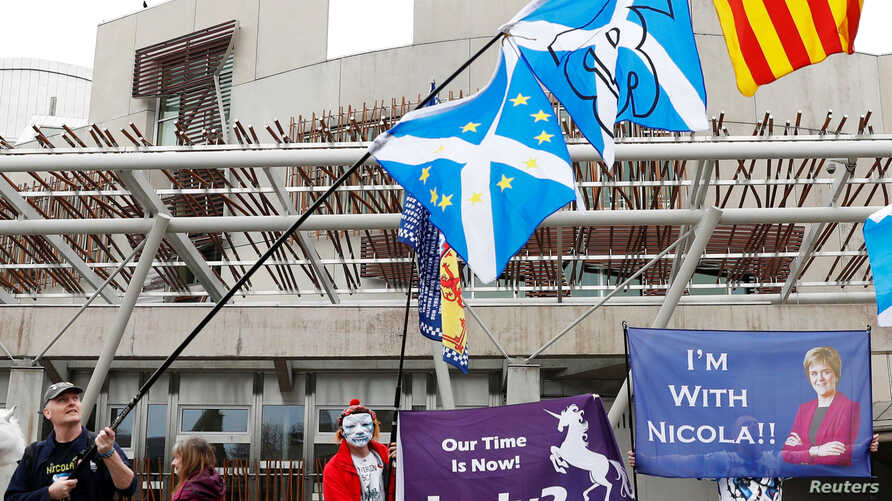 FILE - People hold Saltires and pro-independence flags outside Scotland's Parliament in Holyrood, Edinburgh, Britain, March 28, 2017.
