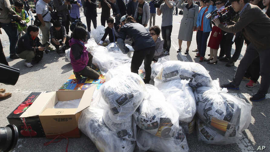 North Koran defectors carry plastic bags of leaflets condemning Pyongyang's  government policies. Leaflets attached to balloons get sent from the border town of Paju, South Korea, on Oct. 10, 2014.