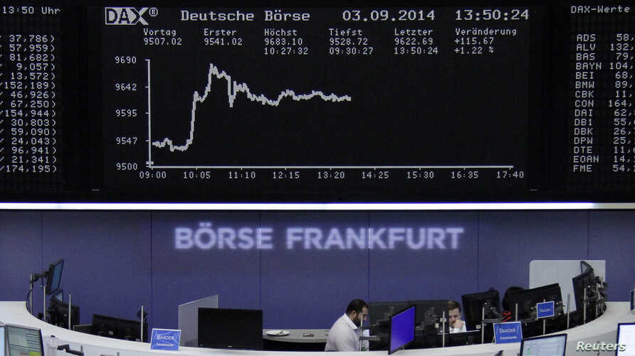 Traders at their desks in front of the DAX board at the Frankfurt stock exchange in Germany, Sept. 3, 2014.