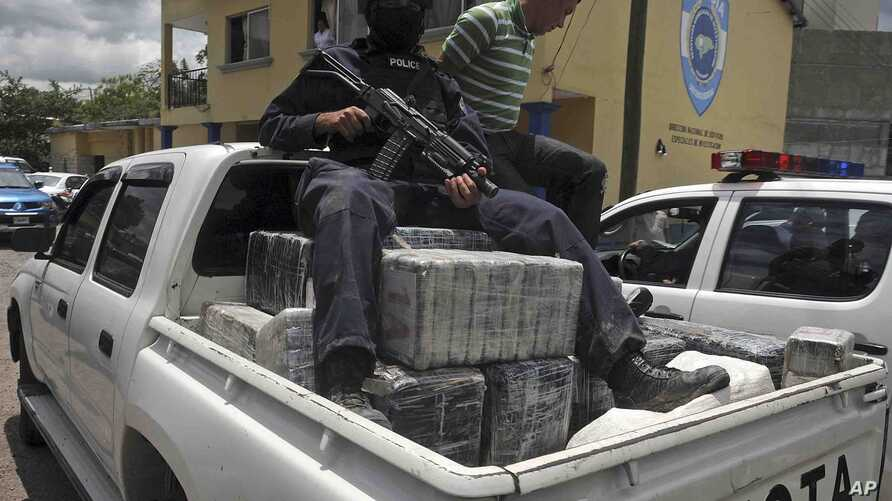FILE - A Honduras national policeman sits on packages of cocaine that were brought to Tegucigalpa, Honduras, July 3, 2012. The cocaine was seized from a small airplane that crashed after it was being chased by military planes and helicopters of the H