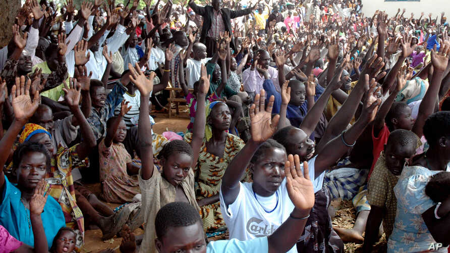 2007 FILE - Members of the LRA community living at Koch Goma IDP camp in Gulu, Northern Uganda raise their hands after having been asked if they were ready to forgive the atrocities of the past twenty years, everyone raised his hand.