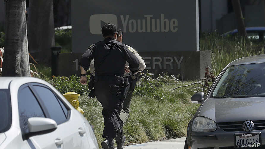 Officers run toward a YouTube office in San Bruno, California, April 3, 2018.