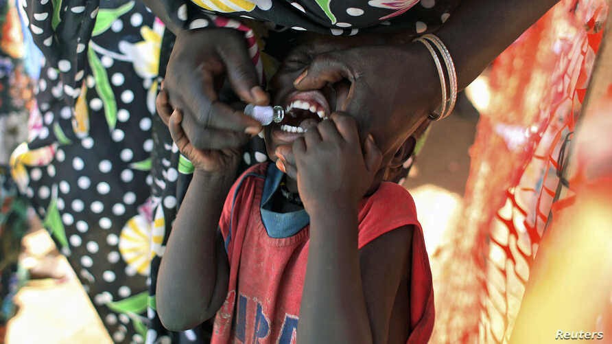 A displaced South Sudanese child receives an oral cholera vaccine in a camp for internally displaced people in the United Nations Mission in South Sudan compound in Tomping, Juba, February 2014.