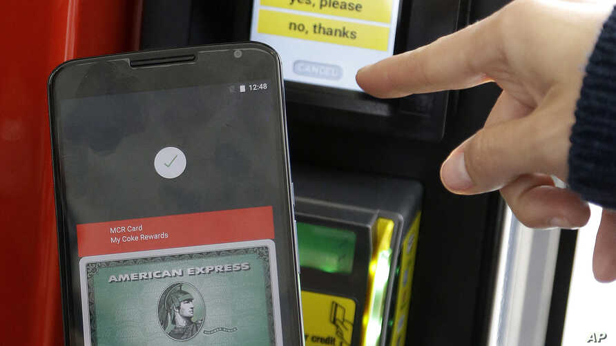 FILE - A Google employee gives a demonstration of Android Pay on a phone at Google I/O 2015 in San Francisco, May 28, 2015.