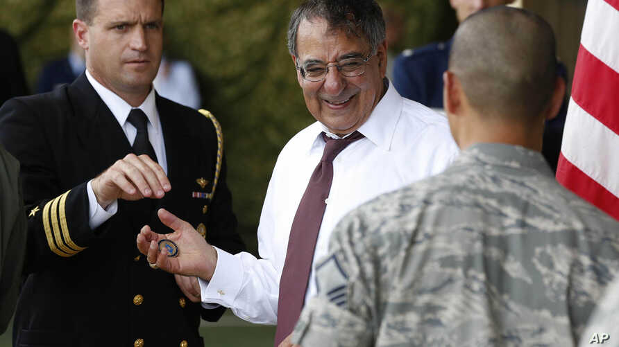 U.S. Secretary of Defense Leon Panetta, center, prepares to give a 'Challenge Coin' to U.S. military personnel stationed at Yokota Air Base in Yokota, Japan, Sept. 17, 2012.
