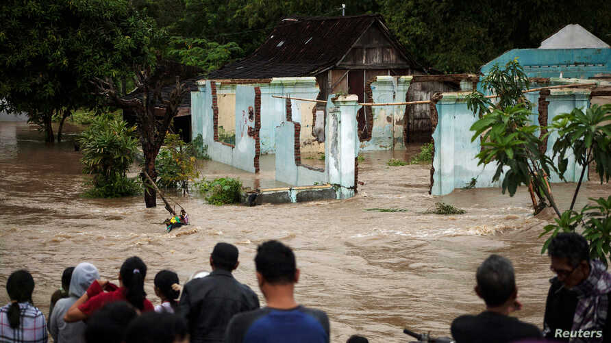 People stand in front of a flooded area in Kampung Sewuresidential area in Solo, Central Java province, Indonesia, June 19, 2016.
