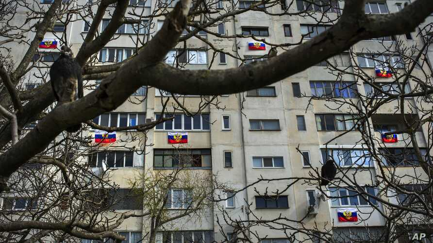 FILE - Russian flags are seen hung from an apartment building in a residential district in Sevastopol, Crimea, March 14, 2014.