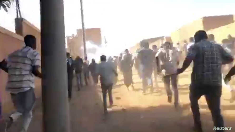 People run as tear gas canisters are thrown at them during an anti-government protest in Omdurman, Sudan, Jan. 9, 2019, in this still image taken from social media.