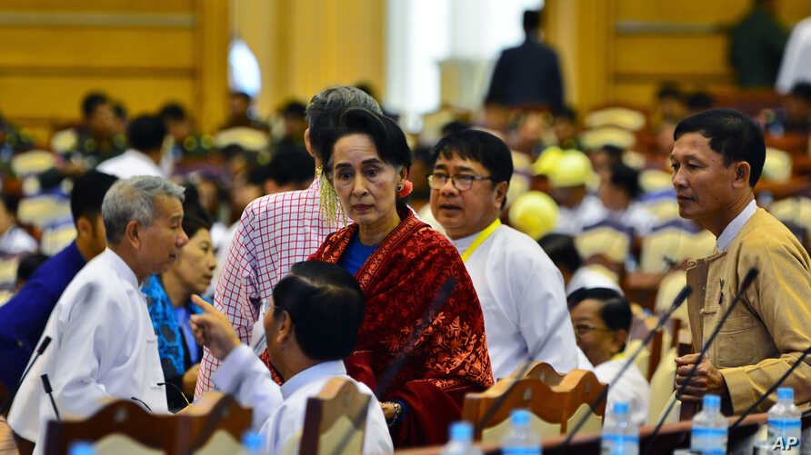Leader of the National League for Democracy party (NLD) Aung San Suu Kyi, covered in a red-scarf stands among the lawmakers of the NLD ahead of a regular session of Myanmar's Lower House parliament in Naypyitaw, Myanmar, Thursday, Jan. 7, 2016.