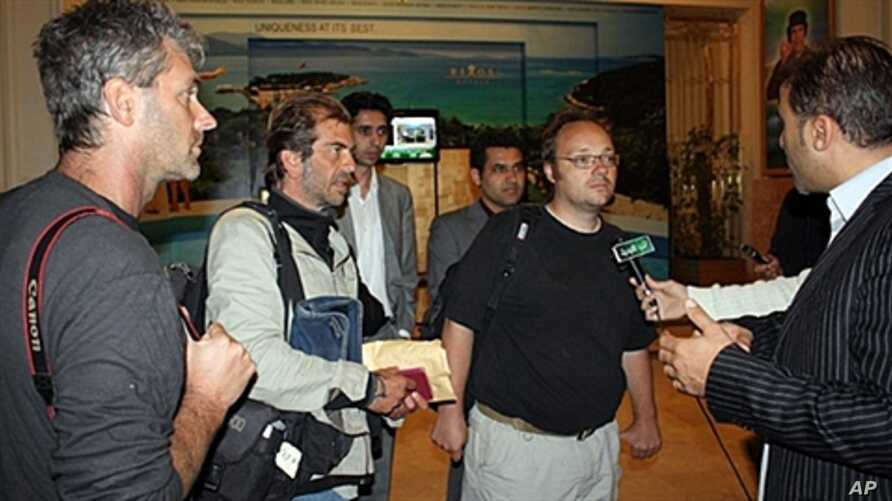 Freed journalists from Agence France Press (AFP) Roberto Schmidt (C) and Dave Clark (2nd-R) and Getty photographer Joe Raedle (L) speak to the press after their release in Tripoli, March 23, 2011