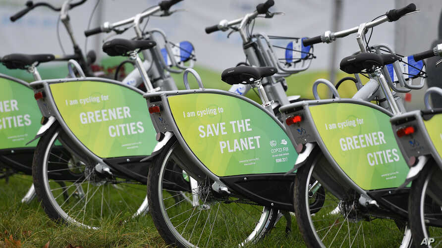 """Bicycles reading """"save the planet"""" wait for customers at the COP 23 Fiji UN Climate Change Conference in Bonn, Germany, Nov. 6, 2017."""