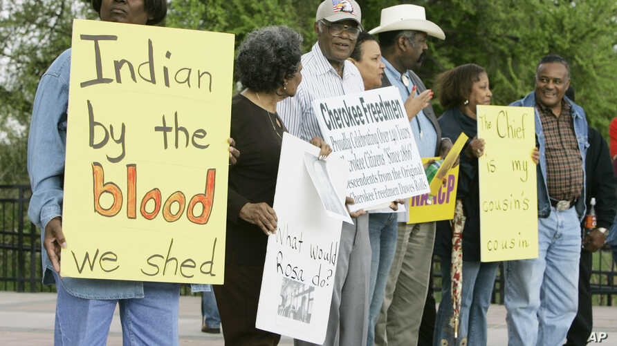 FILE - Waynetta Lawrie, left, of Tulsa, Oklahoma, stands with others at the state Capitol in Oklahoma City during a demonstration by several Cherokee Freedmen and their supporters, March 27, 2007.