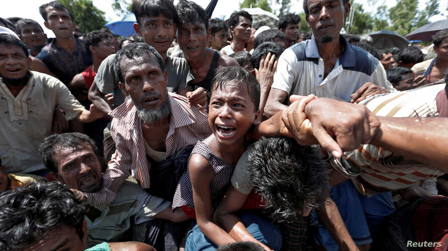 A boy is pulled to safety as Rohingya refugees scuffle while queueing for aid at Cox's Bazar, Bangladesh, Sept. 26, 2017.