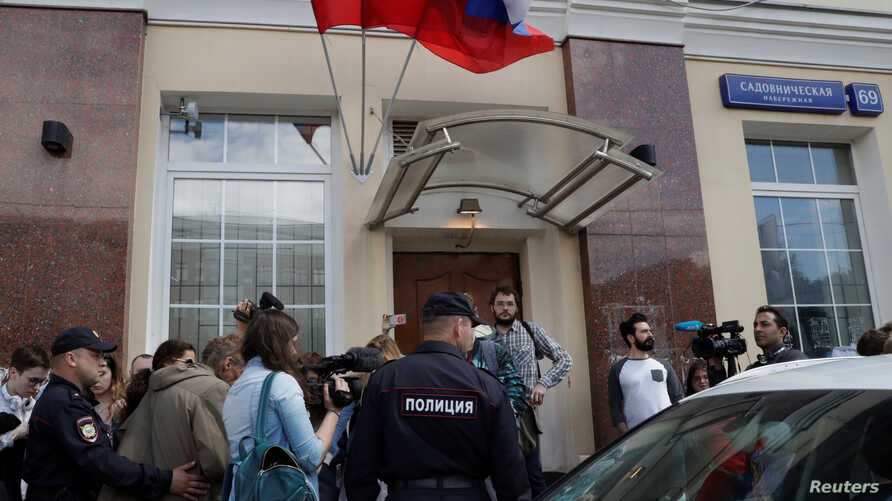 Police officers stand near a group of people gathered in front of a Moscow presidential campaign office for Russian opposition leader Alexei Navalny, where police are conducting an investigation, in Moscow, Russia, July 6, 2017.