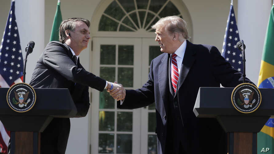 President Donald Trump greets Brazilian President Jair Bolsonaro during a news conference in the Rose Garden of the White House, March 19, 2019.