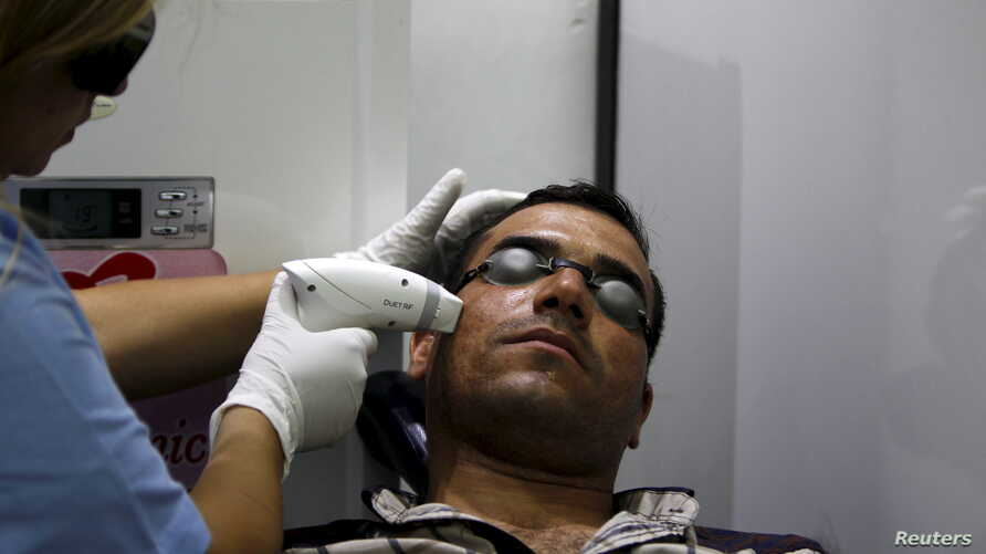 "FILE - A man has acne removed from his face with a laser at a clinic in Baghdad, Iraq, June 2, 2015. Researchers have found that cream personalized with a person's own ""good"" bacteria may help ward off ""bad"" bacteria."
