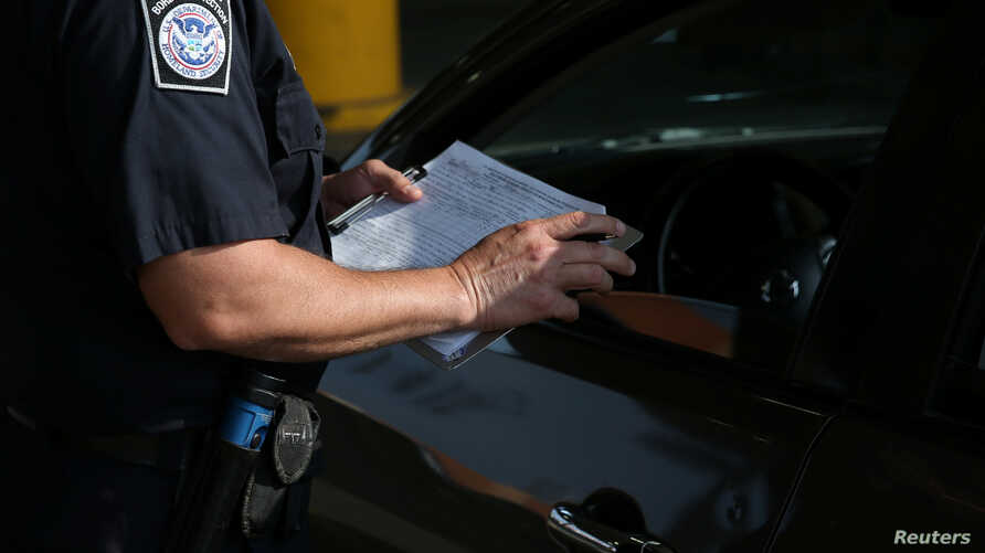 FILE - A U.S. Customs and Border Protection officer works at the Mexico-U.S. border port of entry in Hidalgo, Texas, April 13, 2018.