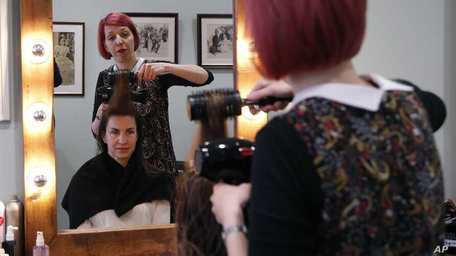 FILE - Lisa Meyer blow drys the hair of a client at her Hair and Beauty shop in London, May 16, 2018.