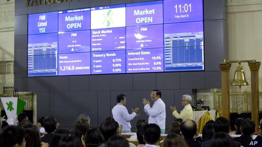 Serge Pun, far right executive chairman of First Myanmar Investment Maung Maung Thein, center Deputy Minister of Finance and Revenue applued after ringing the bell to commence electronic trading during the opening day of trading at Yangon Stock Excha