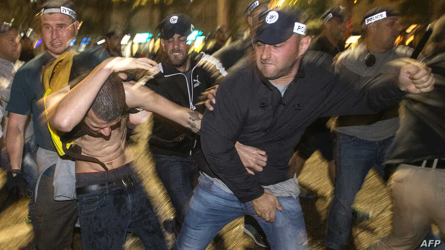 Israeli security forces scuffle with a demonstrater during a protest called by members of the Ethiopian community against alleged police brutality and institutionalised discrimination in the city of Tel Aviv, May 03, 2015.