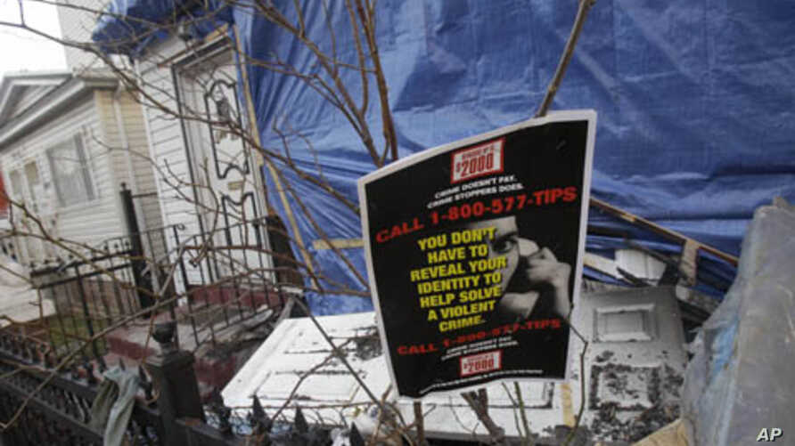 A crime stoppers poster hangs in front of debris outside a fire-damaged home near the Imam Al-Khoei Islamic Center in the Queens, New York, Jan. 2, 2012.