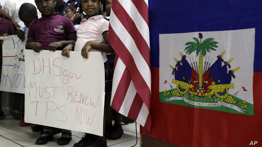 Children stand next to United States and Haitian flags as they hold signs in support of renewing Temporary Protected Status (TPS) for immigrants from Central America and Haiti now living in the United States, during a news conference, Nov. 6, 2017, i