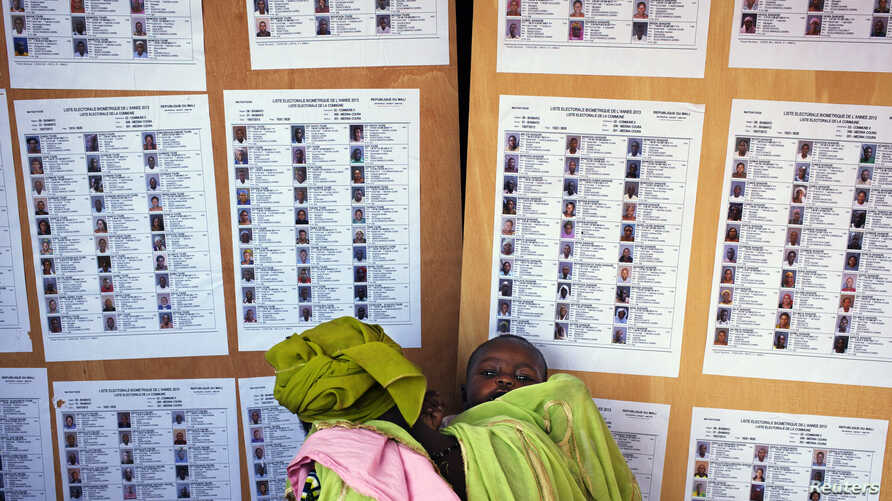 A woman holding a baby searches for her name on a list of eligible voters at an election center in Bamako July 23, 2013. Mali is due to hold presidential elections on Sunday.