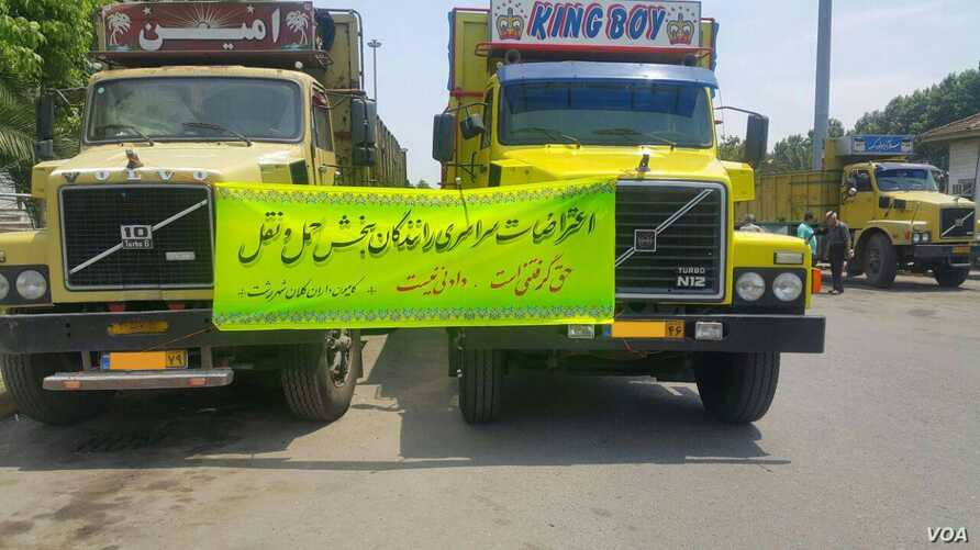 Idled trucks in northern Iran's Rasht city display a sign urging truck drivers to keep up their struggle for better working conditions, in this photo sent to VOA Persian by an audience member and dated May 24, 2018. The license plates have been mostl